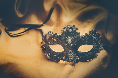 Luxury venetian ball mask on golden silk fabric. Masquerade vintage party or holiday event celebration concept.