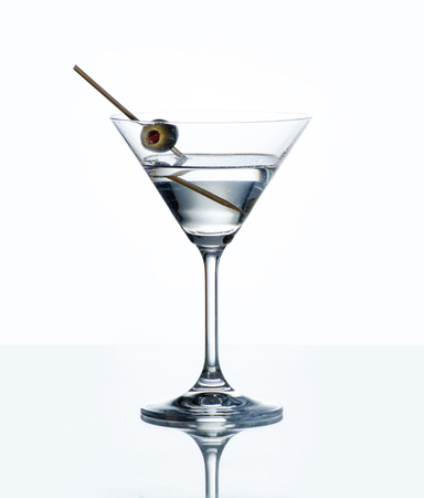 Dry martini with green olive in cocktail glass over white background with reflection. Luxury alcohol drink on bar counter.