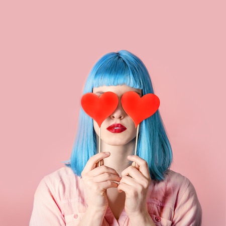 Young stylish woman with blue hairstyle and red lipstick holding valnetine's heart on her eyes. Hipster funny girl model over pink pastel studio background. Love and valentine's day design concept.