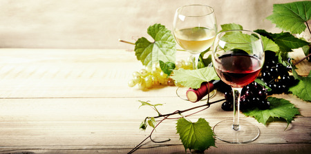 Glass of red and white wine, bottle and grape vine on vintage wooden table. Winery and wine tasting concept. Restaurant vine list design banner background.