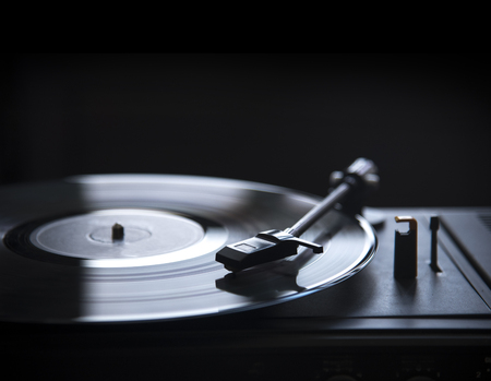Retro gramophone vinyl player over black background with copyspace. Dj music and soundtrack album design. Stock Photo
