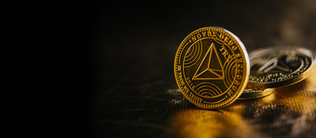 Closeup of golden tron coin  cryptocurrency over black and gold background. Virtual money altcoin and blockchain concept. Banco de Imagens