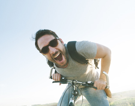 Enthusiastic hipster guy with retro sunglasses having outdoor fun and riding a bicycle. Active sport man with excited face expression exploring and traveling by mountain bike on the road. Vintage film filter style image. Фото со стока