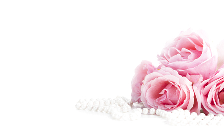 Beautiful pastel pink roses bunch and elegant bridal pearls isolated over white background. Wedding flower bouquet arrangement and classy jewelry. Bright soft clean reception invitation card and banner design.