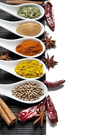 Draufsicht auf gemischte trockene bunte Gewürze in Löffeln isoliert auf weißem Hintergrund. Indisches Essen und orientalische Kochzutaten. Asiatisches Restaurant-Menü-Design. Curry, Chili, Paprika, Pfeffer, Zimt. Standard-Bild