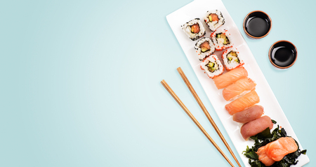Sushi rolls set with salmon and tuna fish on light blue background from above. Top view of traditional japanese cuisine. Asian food restaurant menu modern design.