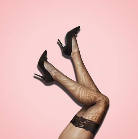 Sexy female legs in fishnet stockings and luxury high heel over pastel studio background. Fashion seductive pantyhose and black woman shoes. Фото со стока