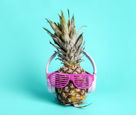 Fashionable  trendy pineapple fruit with headphones and sun glasses listen to the music over bright pastel cyan