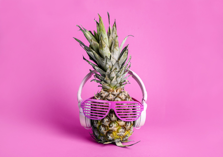 Fashionable  trendy pineapple fruit with headphones and sun glasses listen to the music over bright pastel pink Фото со стока