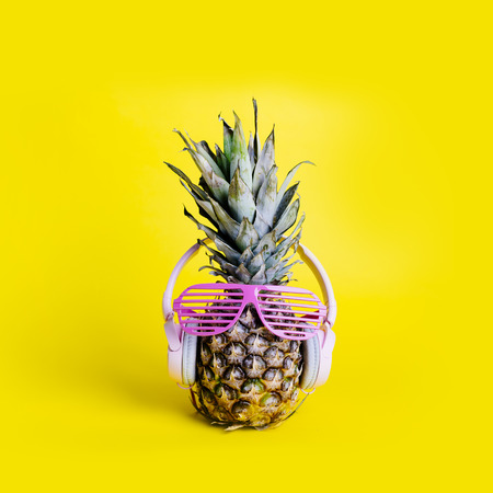 Fashionable  trendy pineapple fruit with headphones and sun glasses listen to the music over bright pastel yellow