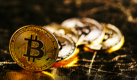 Closeup of golden bitcoin BTC cryptocurrency over black and gold