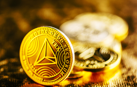 Closeup of golden tron coin TRX cryptocurrency over black and gold