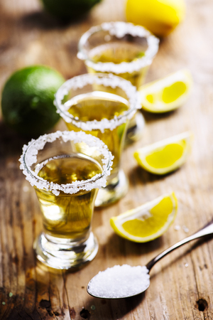 Golden mexican tequila in shot glass with lime and salt on vintage wooden table.