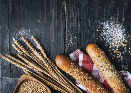 Fresh french baguette bread, organic flour and wholegrain wheat on dark vintage wooden board form above.