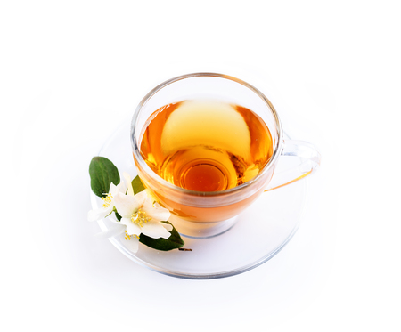 Asian green tea with jasmine flower in transparent teacup isolated on white background with reflection. Traditional chinese hot beverage in glass cup overhead. Organic healthy herbs for alternative medicine. Top view.