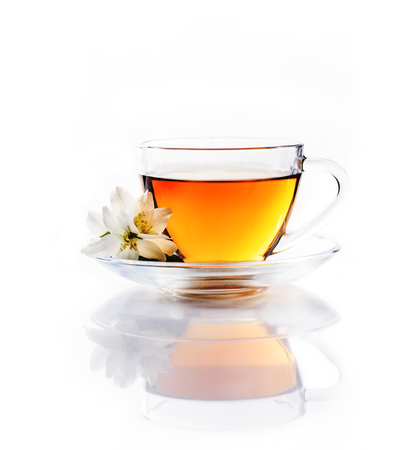 Asian green tea with jasmine flower in transparent teacup isolated on white background with reflection. Traditional chinese hot beverage in glass cup. Organic healthy herbs for alternative medicine