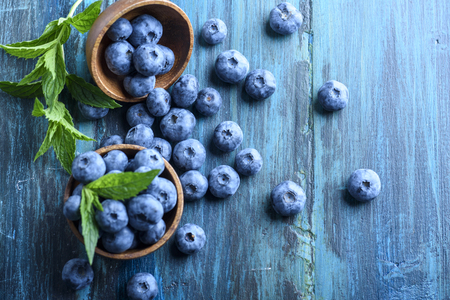 Bowl of fresh blueberries on blue rustic wooden table from above. Top view of healthy organic seasonal fruit pattern background. Organic food blueberries and mint leaf overhead for healthy lifestyle. Фото со стока