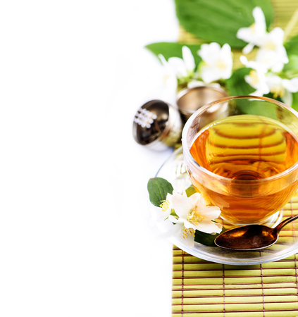 Herbal green tea with jasmine flower in transparent teacup border isolated on white background with cpyspace. Traditional asian hot beverage in glass cup. Organic healthy herbs for alternative medicine.