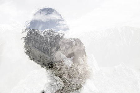 Double exposure with young woman and mountains.