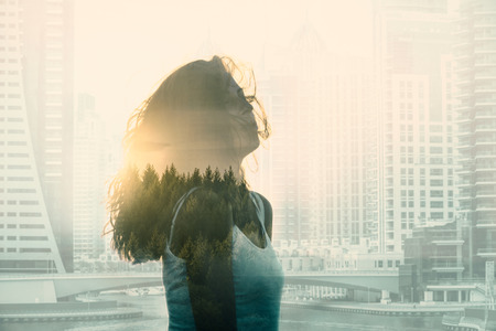 Double exposure with young woman in the modern cityscape and forest. Escape from the city concept.