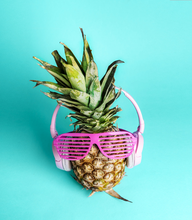 Fashionable trendy pineapple fruit with headphones and sun glasses listen to the music over bright pastel cyan Banco de Imagens
