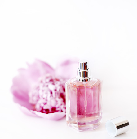 Luxury perfume bottle and pink peony flower isolated on white