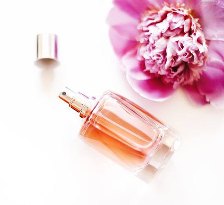 Top view of luxury perfume bottle and pink peony flower on white