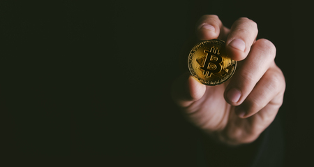 Closeup of golden bitcoin BTC cryptocurrency in hand over dark black