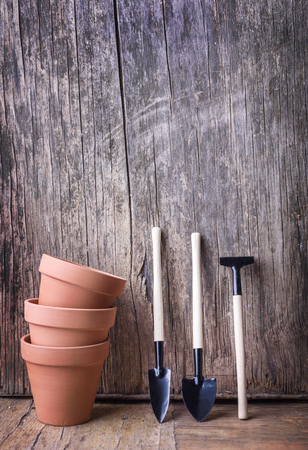 Plant clay pot and gardening tool on vintage wooden Banco de Imagens
