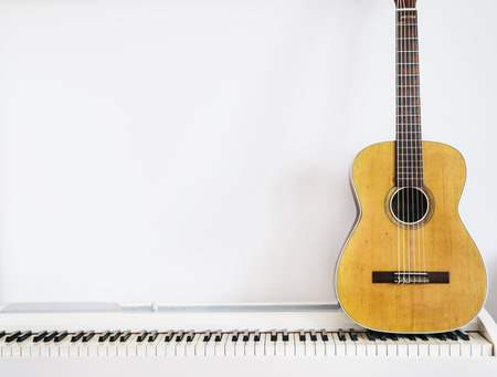 Acoustic guitar on piano keyboard in front of white wall. Standard-Bild