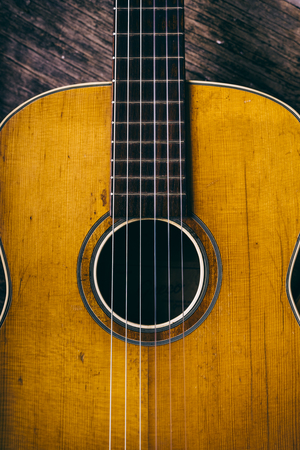 Closeup of wooden acoustic guitar from above.