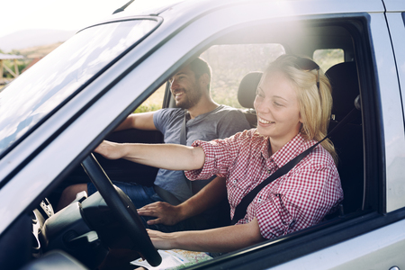 Happy couple traveling by car in nature. Carefree friend travelers on countryside roadtrip journey. Young woman and man driving on romantic weekend. Banco de Imagens