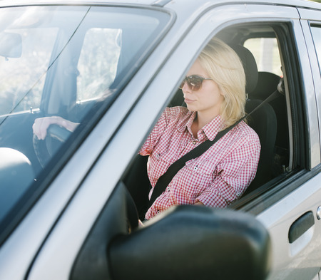 Young blond woman driving a car. Casual girl with sunglasses traveling in vehicle. Banco de Imagens