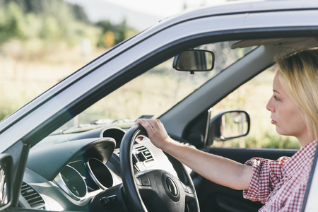 Young caucasian blond woman traveling by car and having fun on her summer holiday journey. Happy girl driving car on countryside road. Roadtrip vacation.