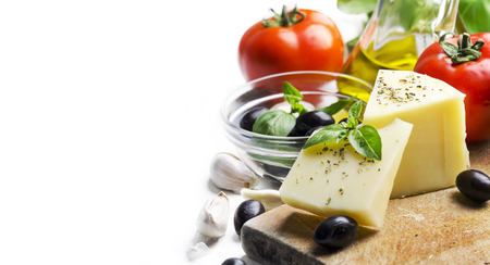 Goat cheese, olives, olive oil, tomato, garlic, basil and spices on wooden cutting board isolated on white background. Food ingredients for italian pizza recipe. Mediterranean cuisine with dairy product and organic vegetable and herbs.