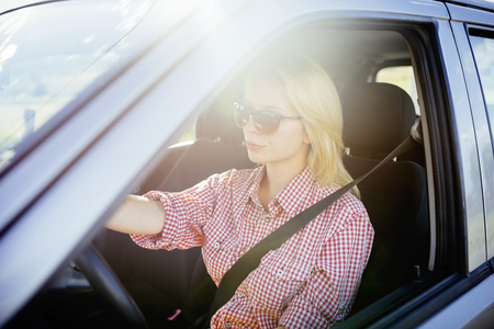 Happy young woman driver driving her new luxury car. Summer roadtrip travel and people lifestyle concept. Banco de Imagens