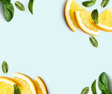 Citrus slices and mint herbs frame on retro mint pastel background with copyspace from above. Top view of lemon and orange refreshment. Summer fruit smoothie minimal banner design. Flat lay. Banco de Imagens
