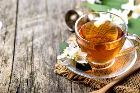 Herbal green tea border on wooden rustic background. Hot cup of jasmine tea on vintage textured table from above. Asian organic detox beverage. Alternative medicine food and drink concept.