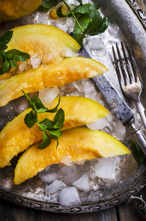 Top view of cantaloupe melon slices with mint and ice served  on vintage sliver plate. Sweet fruit dessert still life from above.