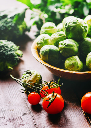 Brussel sprout, cherry tomato, broccoli, parsley and greens on rustic wooden table. Superfood vegetable salad mix on vintage background. Closeup of healthy food ingredients still life. Organic and vegan recipe cuisine concept.