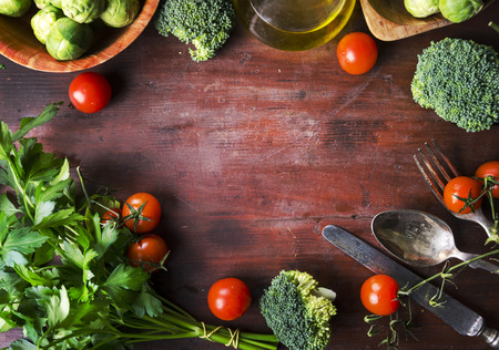 Top view of healthy food ingredients frame on vintage wooden table. Superfood vegetable mix border on rustic background from above. Cherry tomato, sprout brussels, broccoli, parsley, greens and olive oil overhead.