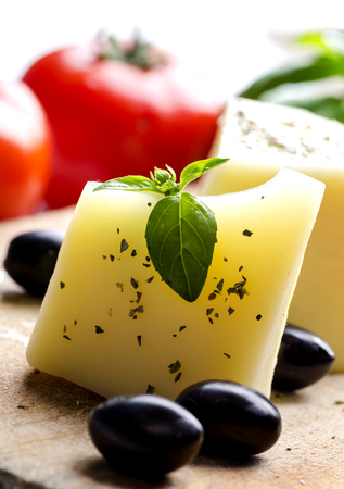 Closeup of goat cheese, olives, fresh tomato, basil and spices on wooden cutting board. Food ingredients for italian pizza recipe. Mediterranean cuisine with dairy product and organic vegetable and herbs.