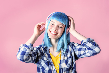 Trendy young woman with blue dyed listen to music and dancing. Hipster girl with headphones over neon pastel background. Banco de Imagens
