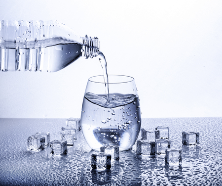Gieten van vers drinkwater mineraalwater uit plastic fles. Glas gevuld met water op witte achtergrond.