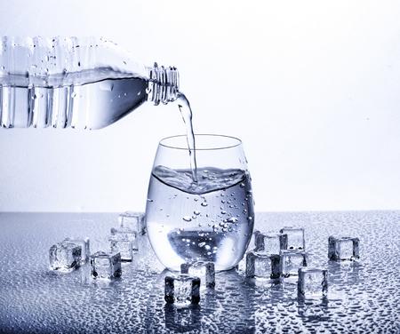 Versando acqua minerale fresca potabile dalla bottiglia di plastica. Vetro riempito d'acqua su sfondo bianco.