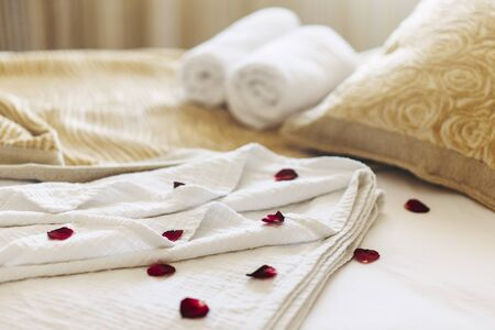 Luxury spa hotel room for romantic weekend. Honeymoon suite bedroom decorated with rose petals.