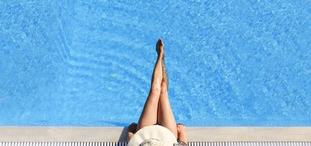 Sexy woman in bikini and sunhat relaxing in swimming pool. Banco de Imagens