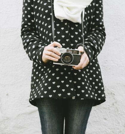 Young hipster woman holding vintage photo camera. Retro camera in girl hand closeup. Banco de Imagens