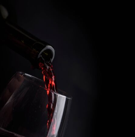 Red wine pouring in wineglass from bottle over black