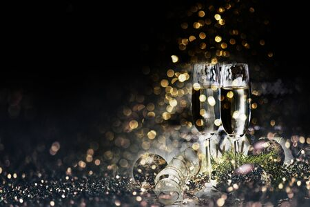 Two champagne glasses and christmas decoration over dark golden bokeh